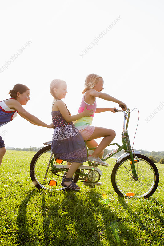 Girls playing with bicycle in grass