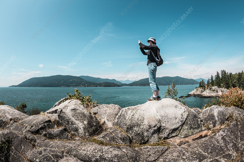 Woman taking pictures of rural lake