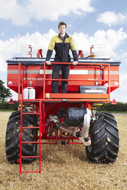 Farmer standing on tractor in field