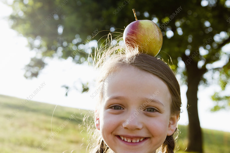Smiling girl balancing apple on head