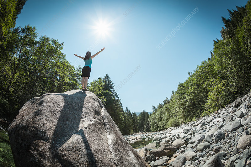 Woman with arms outstretched on rock