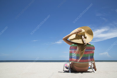 Woman relaxing in lawn chair on beach