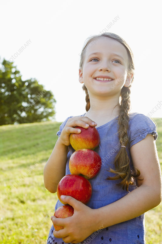 Smiling girl carrying apples outdoors