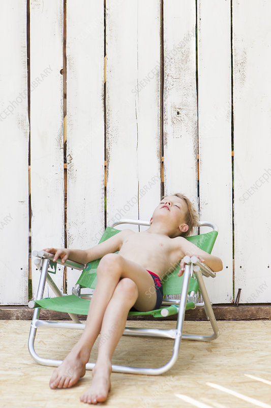 Boy in swimsuit in lawn chair indoors
