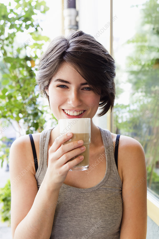 Smiling woman drinking coffee outdoors