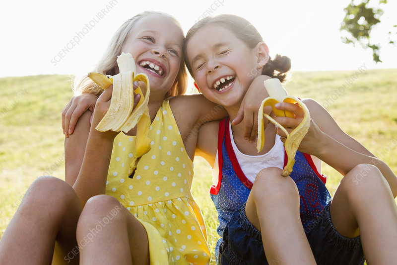 Laughing girls eating bananas outdoors