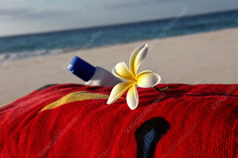 Flower and sunscreen on towel on beach