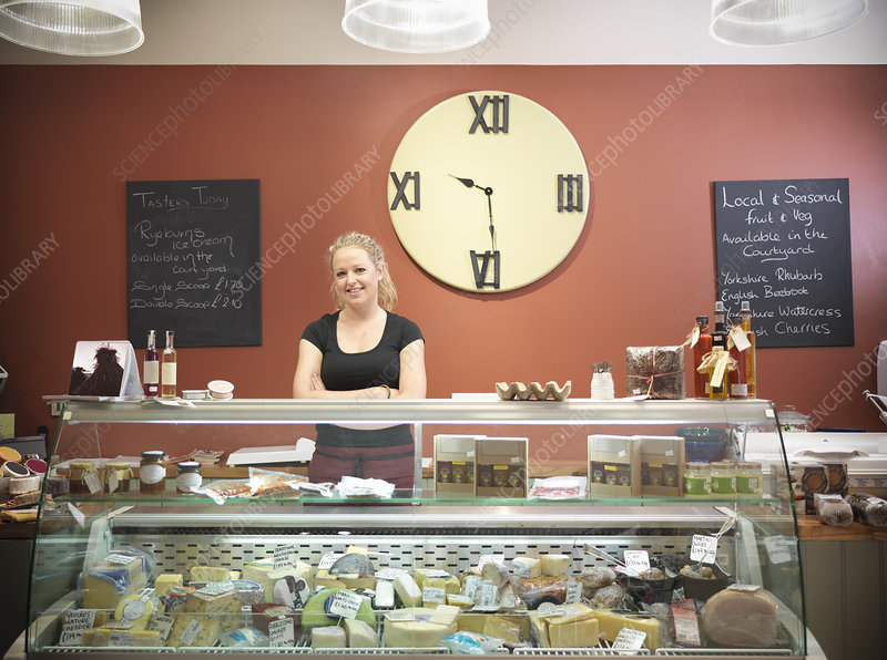 Grocer standing behind counter in shop
