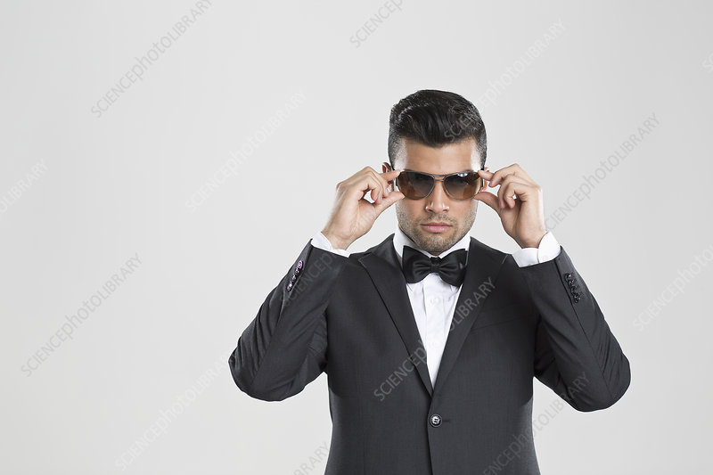 Man in tuxedo adjusting his sunglasses
