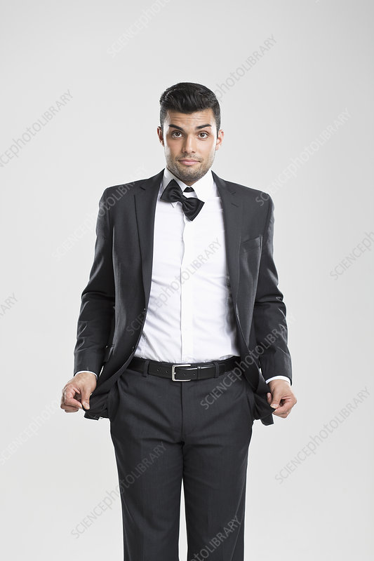 Man in tuxedo pulling at empty pockets
