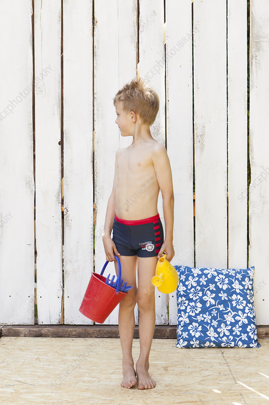 Boy in swimsuit with beach toys indoors
