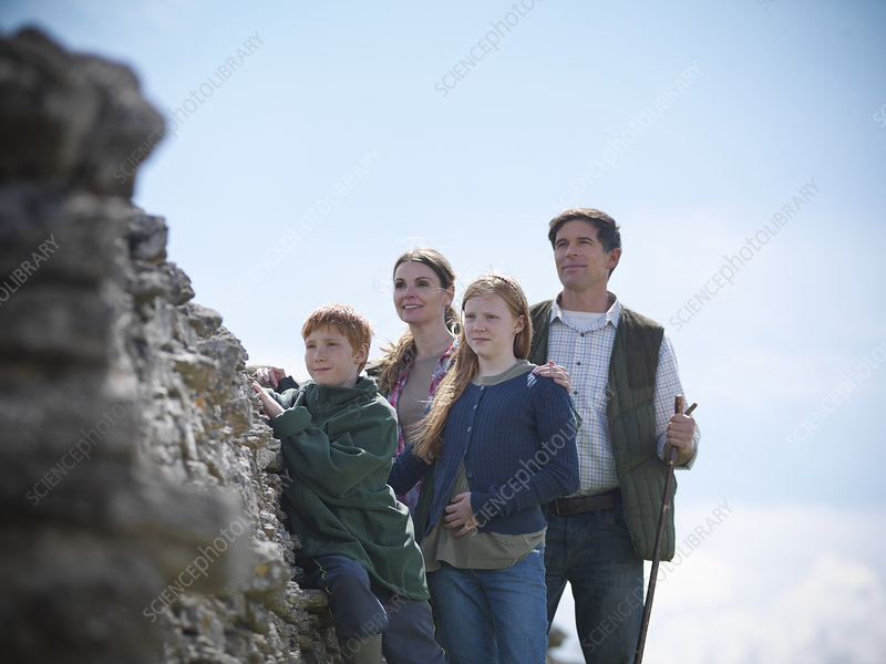 Farmer and family standing by stone wall