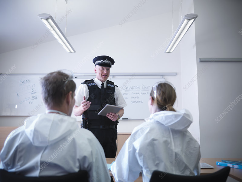 Policeman talking to forensic scientists