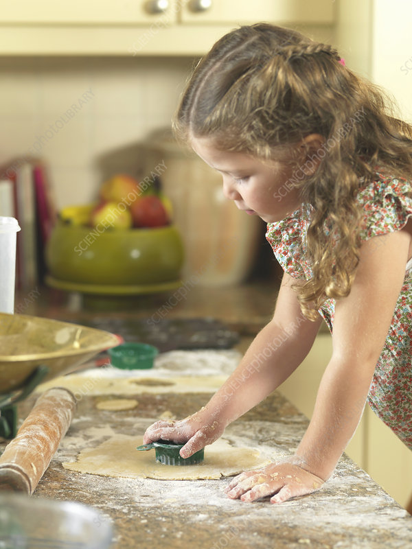 Girl cutting out cookies in kitchen