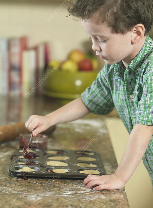 Boy spooning batter into pan in kitchen