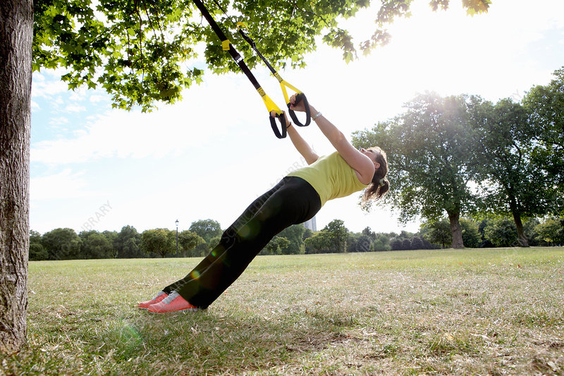 Woman using exercise straps outdoors