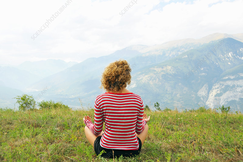 Woman meditating on rural hilltop