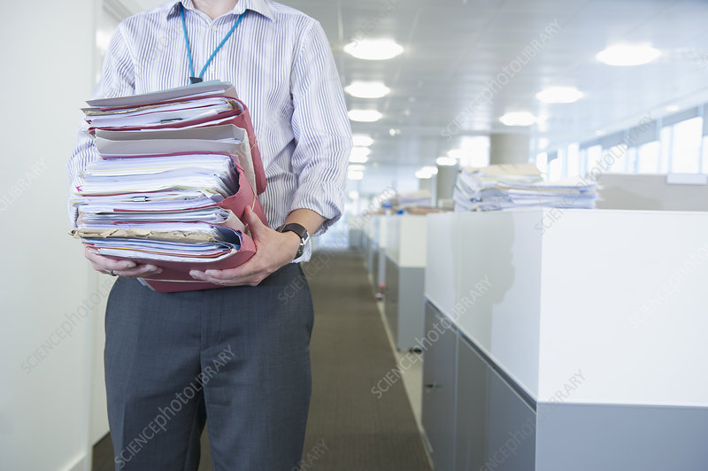 Businessman carrying stacks of papers