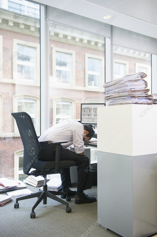 Businessman sleeping at desk in cubicle