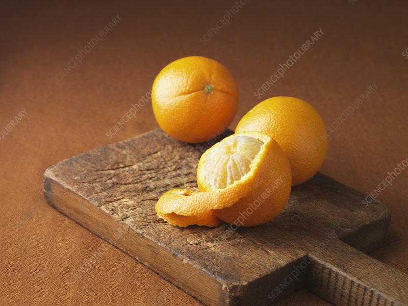 Peeling orange on wooden board