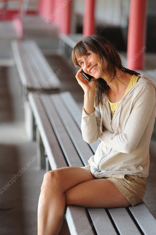 Woman talking on cell phone on bench