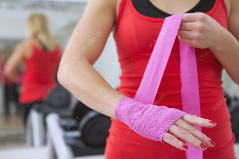 Boxer wrapping her hands in gym
