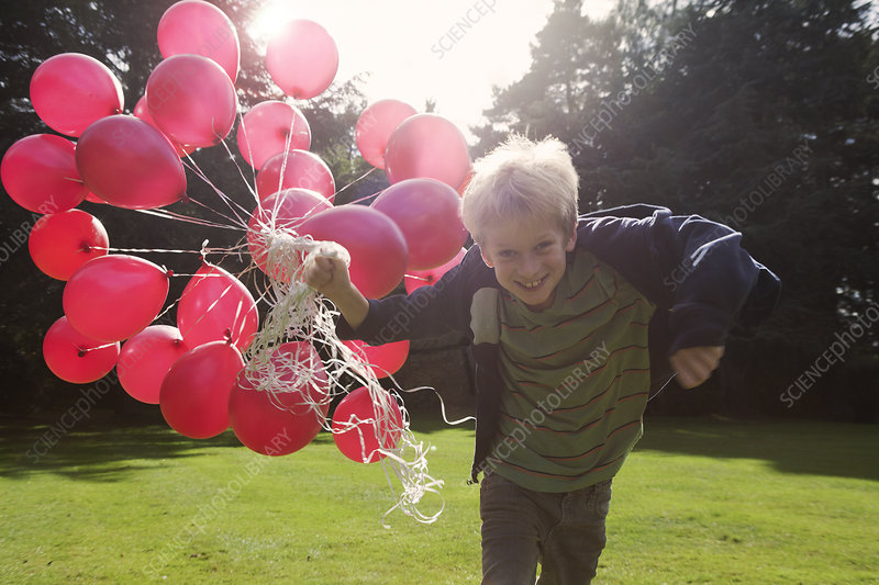 Boy carrying bunch of balloons outdoors