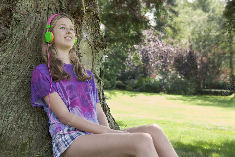 Girl listening to headphones in park