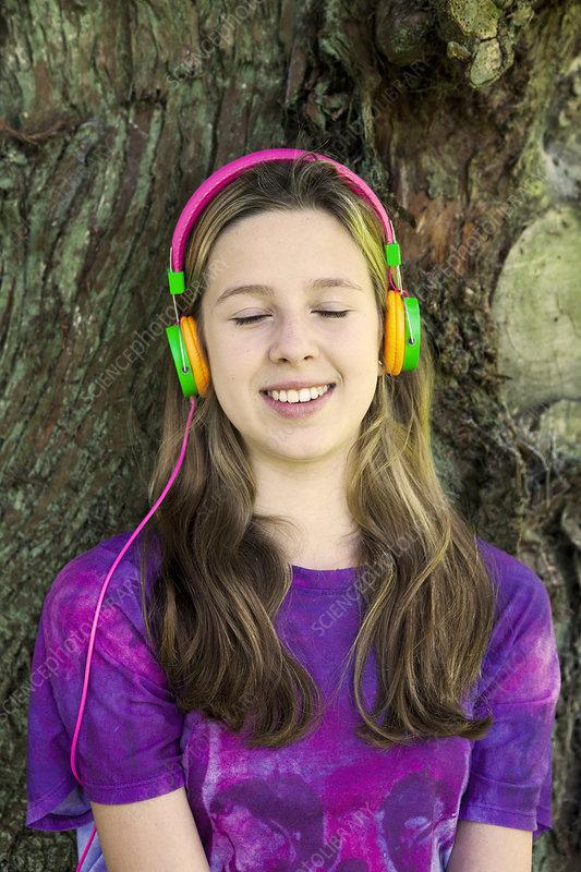 Girl listening to headphones in park
