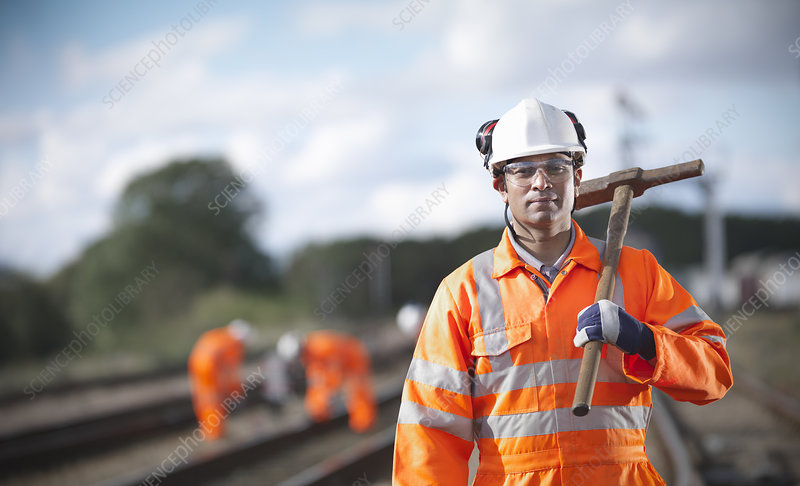 Railway worker carrying sledgehammer