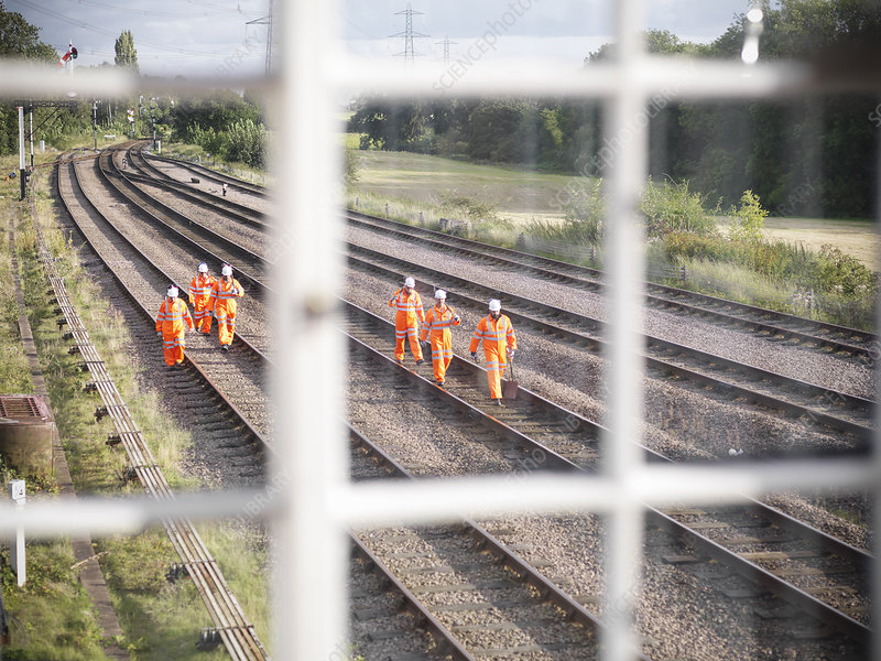 Railway workers walking on train tracks