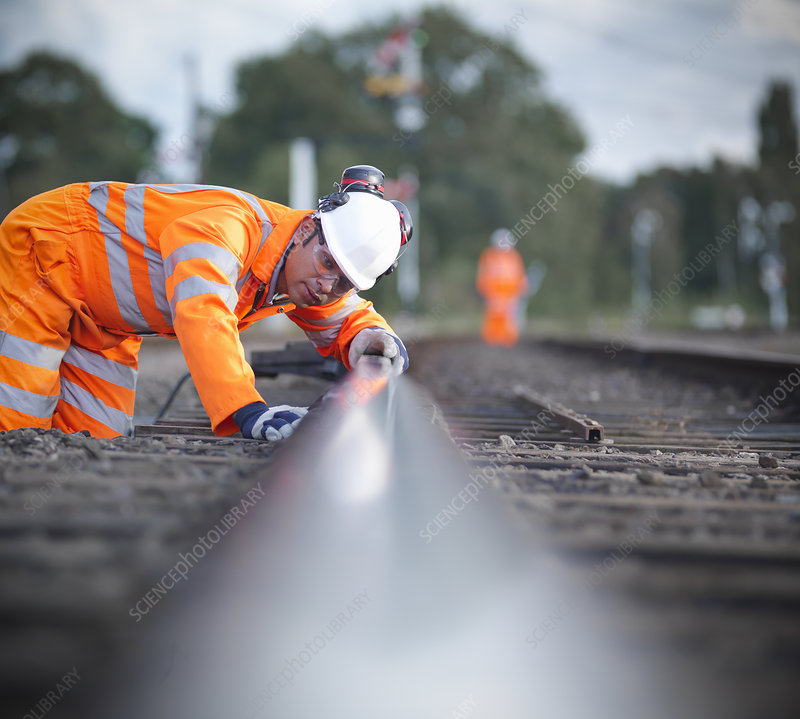 Railway worker examining train tracks