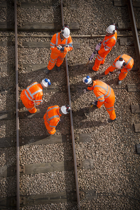 Railway workers examining train tracks