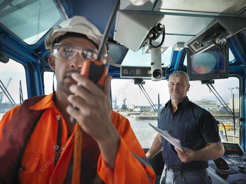Worker talking in tugboat wheelhouse