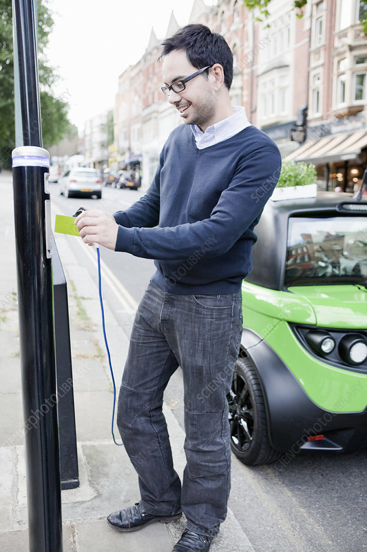 Man charging electric car on street