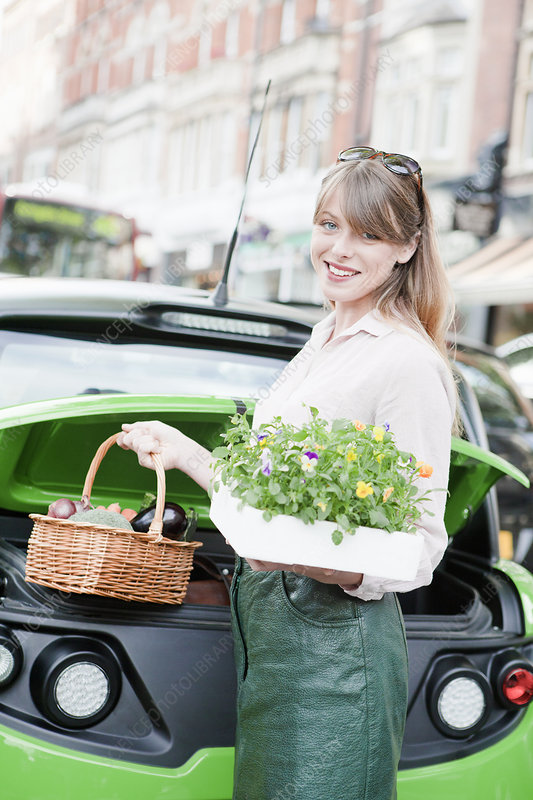 Woman loading produce into car