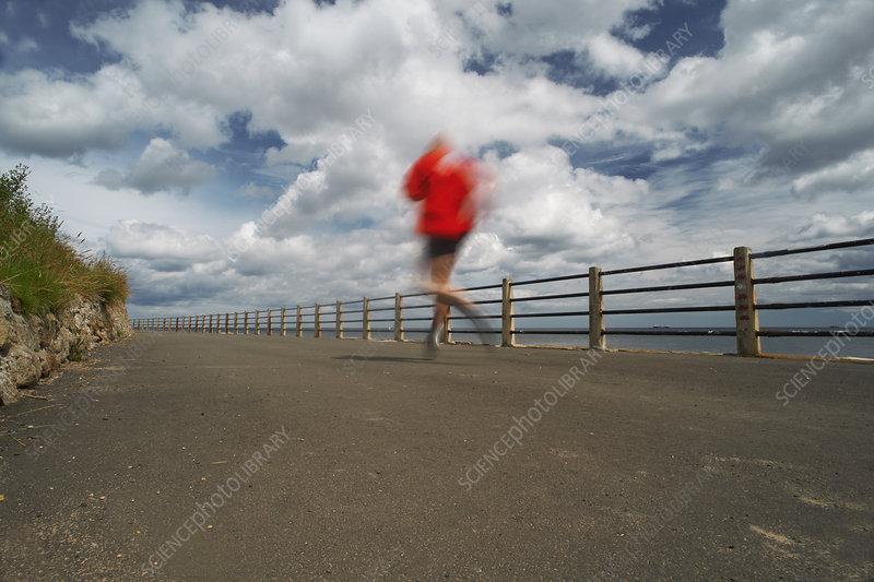 Runner on paved coastal road