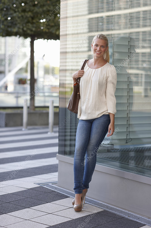 Smiling woman leaning against building