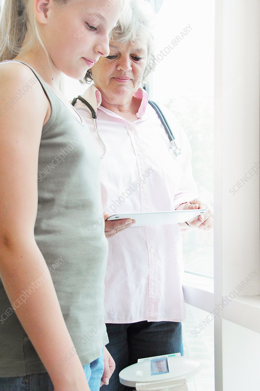 Doctor checking girl's weight