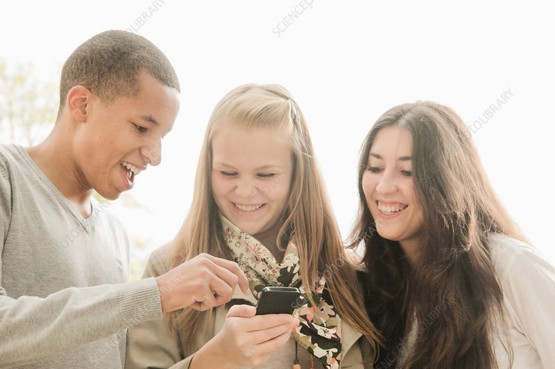 Teenagers using cell phone together