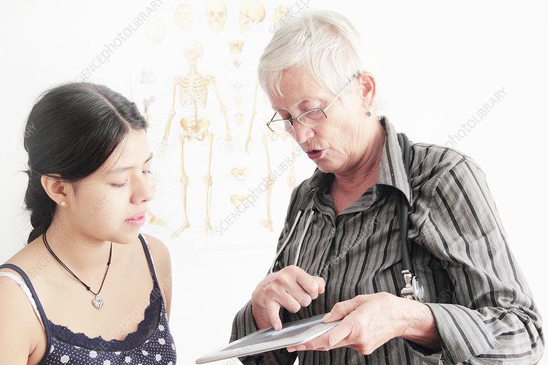 Doctor showing x-ray to teenage girl