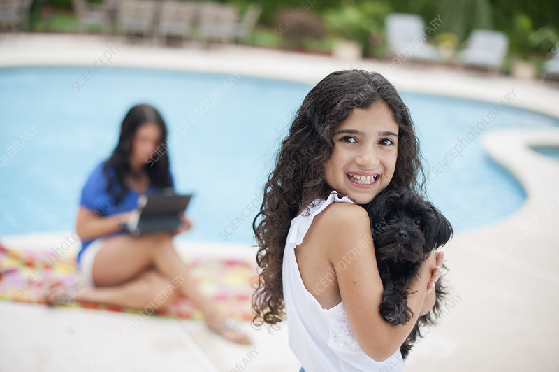 Smiling girl holding puppy by pool