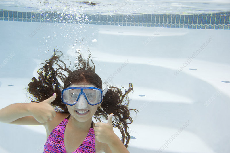Girl giving thumbs up underwater