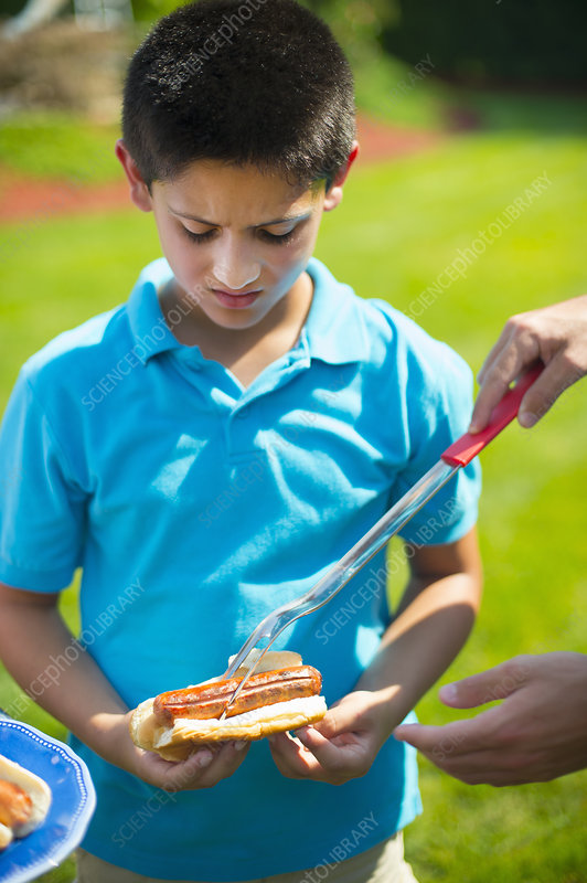 Man serving son hot dog outdoors