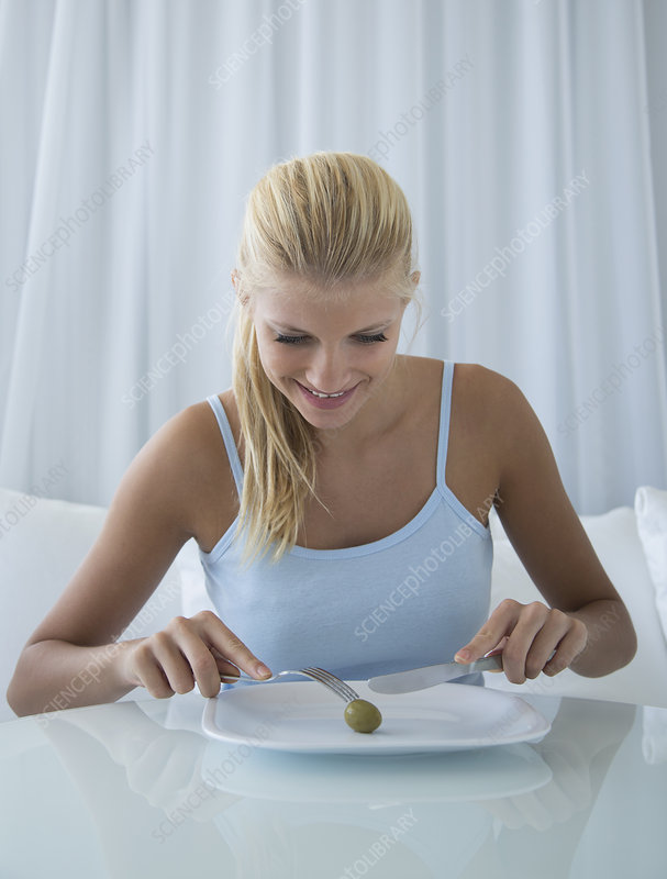 Smiling woman slicing olive on plate