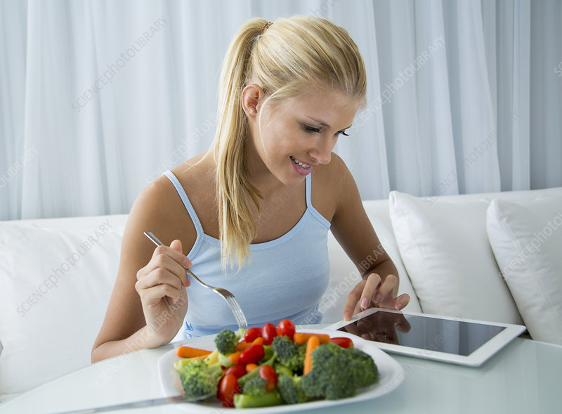 Woman using tablet computer and eating