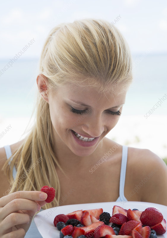 Smiling woman eating plate of fruit