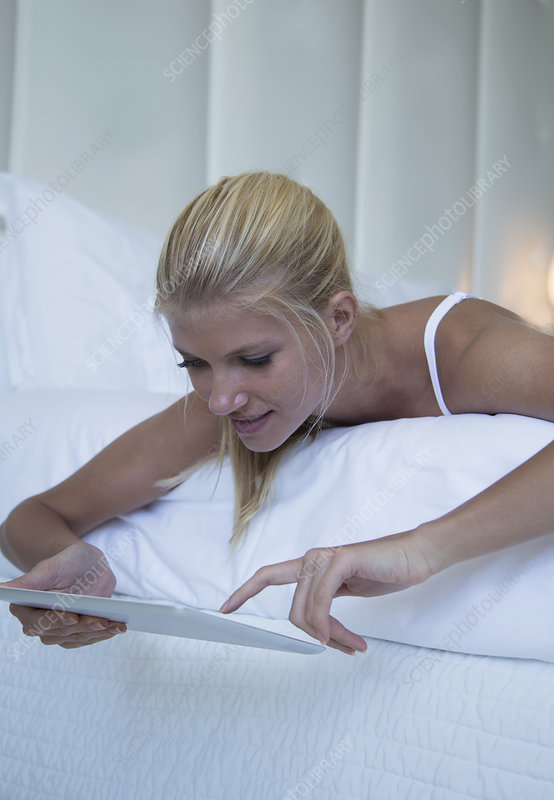 Woman using tablet computer on bed
