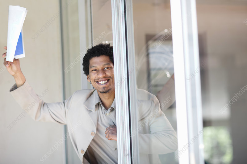 Businessman leaning in glass door