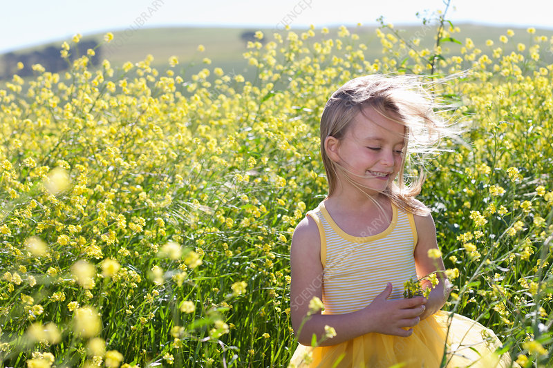 Smiling girl playing in field of flowers